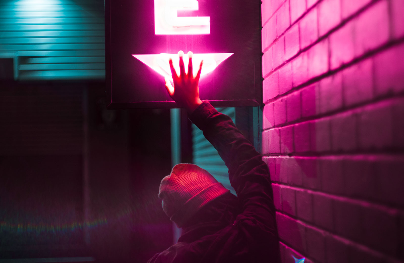Back view of a person in a beanie with hand raised covering pink neon light sign symbolising digital life & it's activation