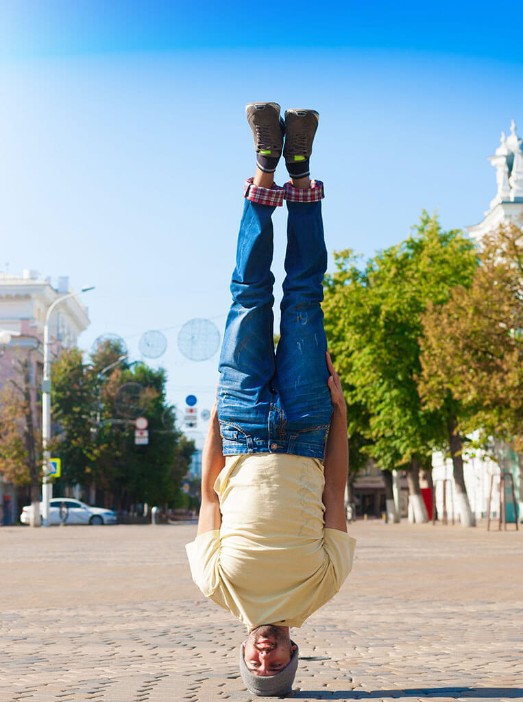 Man, preforming handsfree headstand on an urban cityscape just like us ensuring that no detail is missed on your Creative quest
