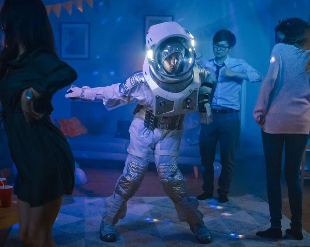 Colleague's wearing Space suit, data analyst and philosopher costumes doing the robot dance in a Neon lit work party